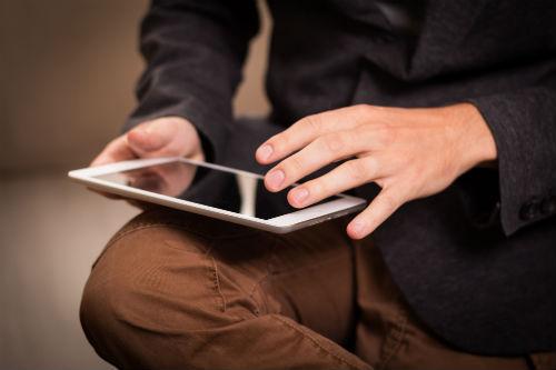 Bild på ett person med en läsplatta i knät
