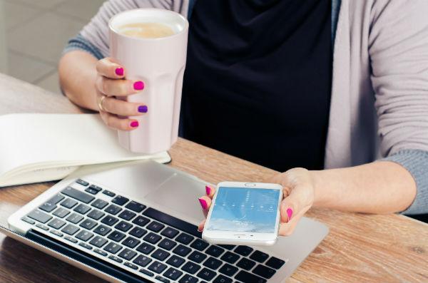 Ung kvinnan med en mugg kaffe i ena handen. I andra handen en mobiltelefon. Hon sitter framför en dator.