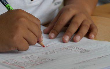 Bild på två händer. I den ena handen håller personen en penna.