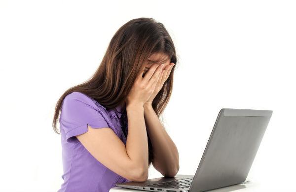 Elev som sitter vid en dator med händerna framför ansiktet