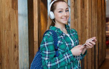 Tonåring med med vita hörlurar och turkos rutig skjorta